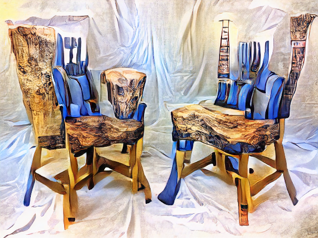 Two chairs face each other. Their seats are thick knotted pieces of wood and their backs are blue cartoonish paint alternating with carved pillars. The legs are highly distorted.