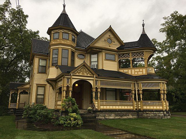 A beige wooden Victorian house with two turrets, long upper and lower balconies, and intricate wooden decorations. It sits on a green lawn surrounded by thin-leafed trees under an overcast sky.