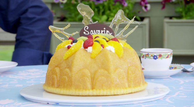 A yellow bundt cake topped with sliced oranges, strawberries, kiwi, and blueberries on top of a thin layer of cream.