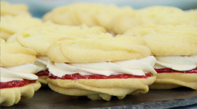 Pale sandwich cookies with a swirl of white frosting and a thin layer of raspberry jam inside.