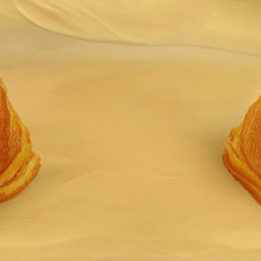 An empty table with the edges of two pastries just visible on either side, almost out of view.