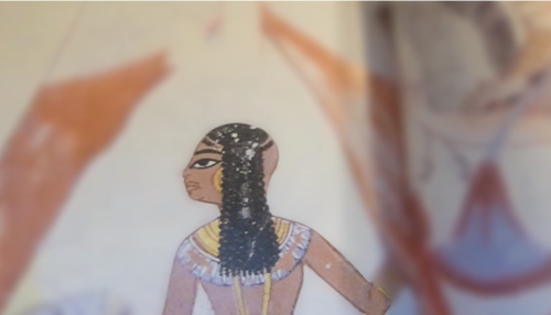 Detail of an ancient egyptian painting. The person's face and body are in focus, but forearm is blurred.
