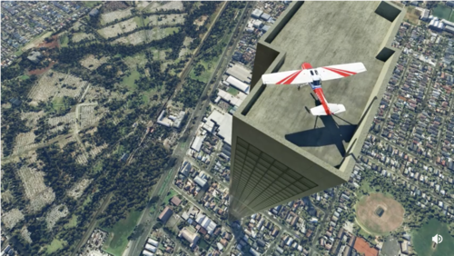 A small two-person plane on the roof of a 212-story building surrounded by a 1-story suburb. View looks steeply down toward the ground. The top of the building seems to be only about an eighth of a city block in size