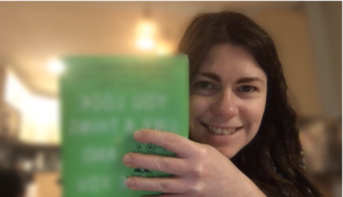 Janelle is holding up her book. The cover is blurred, except for a tiny slice between her fingers